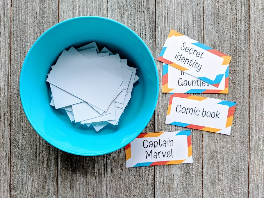 Overhead view of small round blue bowl with rectangle slips of paper inside. Next to the bowl are several pieces of paper with superhero theme words cut from printable charade word list.