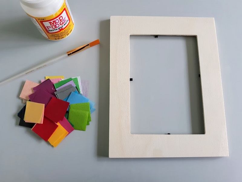 Overhead view of empty plain wooden picture frame laying on craft mat next to pile of pre-cut tissue paper squares in assorted colors, a paint brush, and a bottle of Mod Podge.