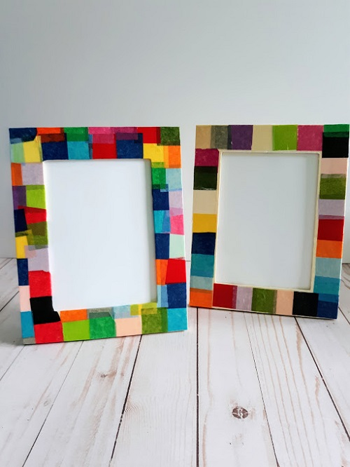 Two completed picture frames decorated with multi-colored tissue paper standing up.