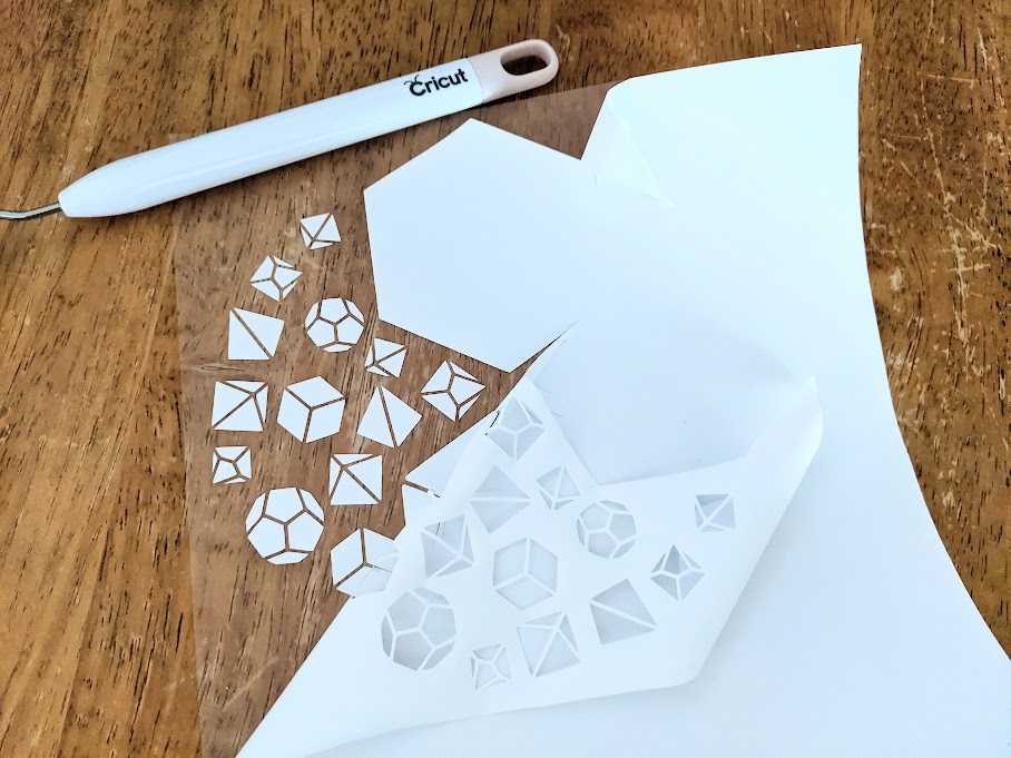 Overhead view of dice design cut on white iron on vinyl partially weeded. Weeding tool laying above design on table.