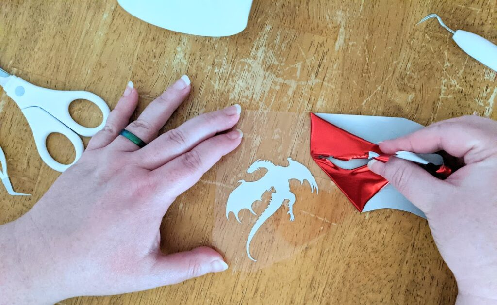 Overhead view of white woman's hands holding iron-on vinyl liner in place while pulling back excess red foil iron on revealing dragon silhouette design.