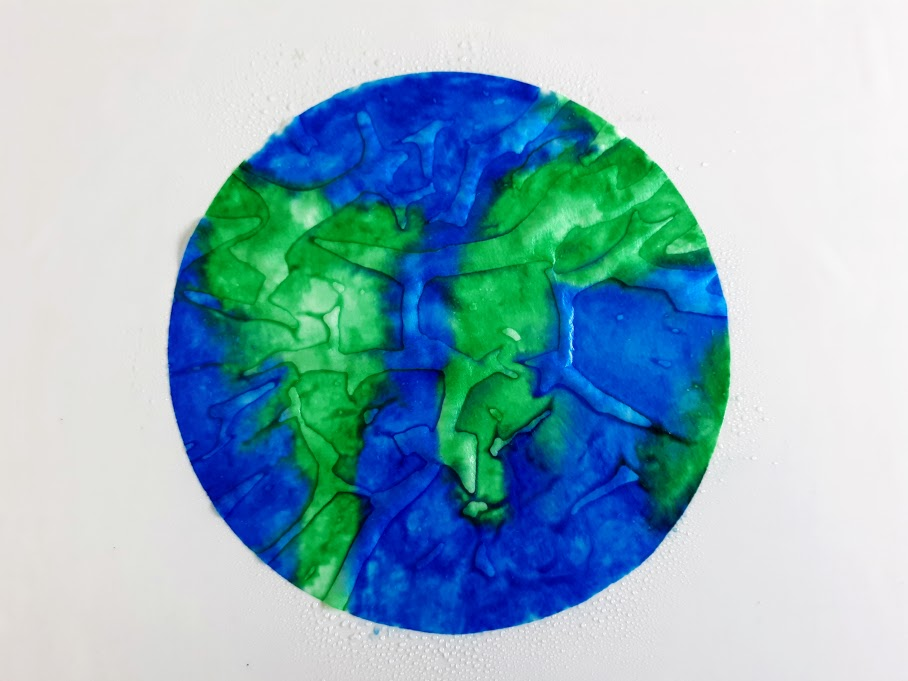 Overhead view of wet coffee filter colored to look like Earth. Entire coffee filter is saturated with water.
