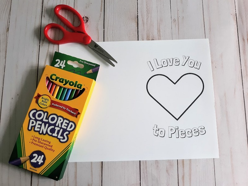 Love to Pieces card printed out and laying flat on table with red handled scissors and a box of colored pencils.