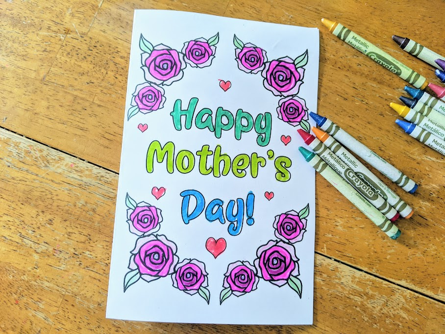 Colored in Mother's Day card laying on table with crayons laying next to it. Card says Happy Mother's Day! on front and has roses and hearts around it.