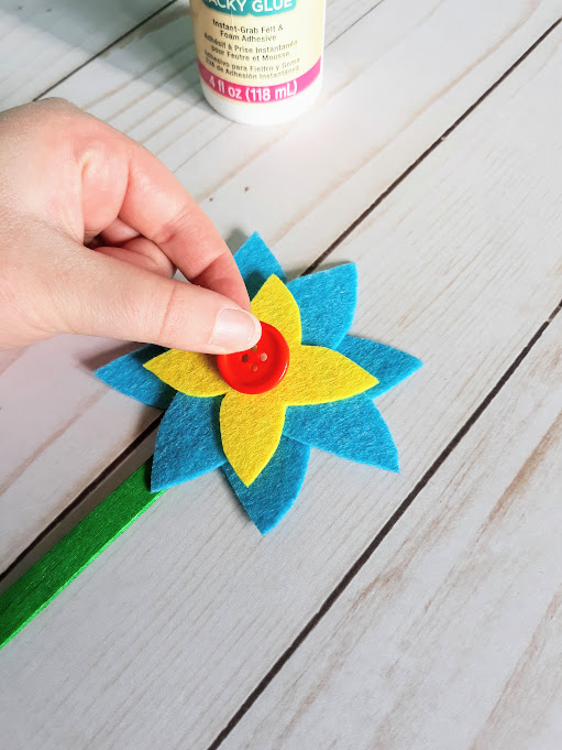 White woman's hand gluing red button to center of yellow and blue felt flower.