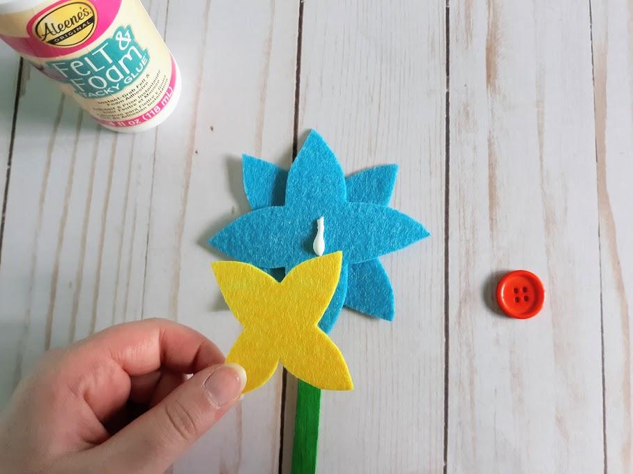 White woman's hand gluing yellow felt petals to blue felt flower.