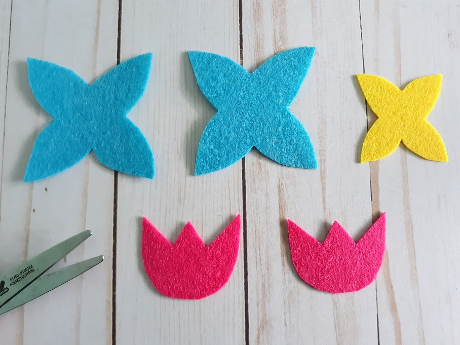 Two blue felt petal sections, one smaller yellow felt petal, and two pink felt tulip shapes cut out.