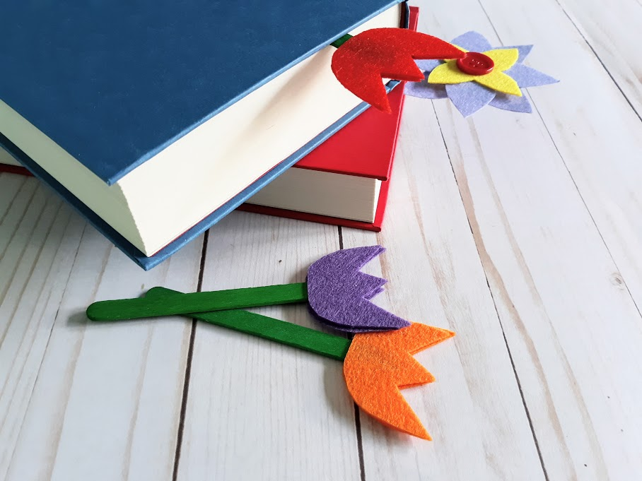 Blue and red hardcover books without dust jackets stacked on top of one another. Multi-petal felt flower bookmark sticking out of bottom book and red felt tulip bookmark sticking out of the top book. Purple and orange tulip bookmarks on green popsicle sticks lay next to the books.