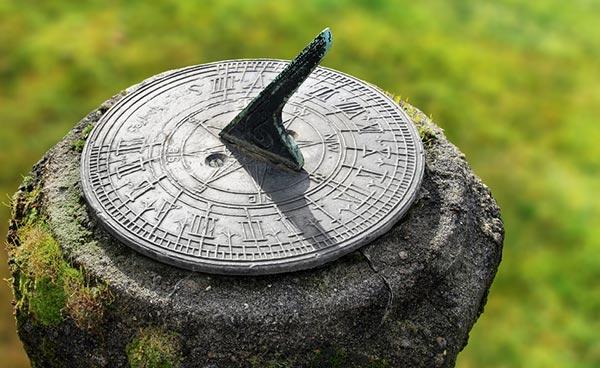 Shadow cast on a garden sundial on a stone pedastal.