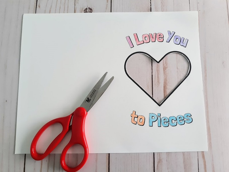Overhead view of printed out card with center heart cut out. I Love You To Pieces words are colored in with colored pencil. Small pair of scissors laying over the paper.