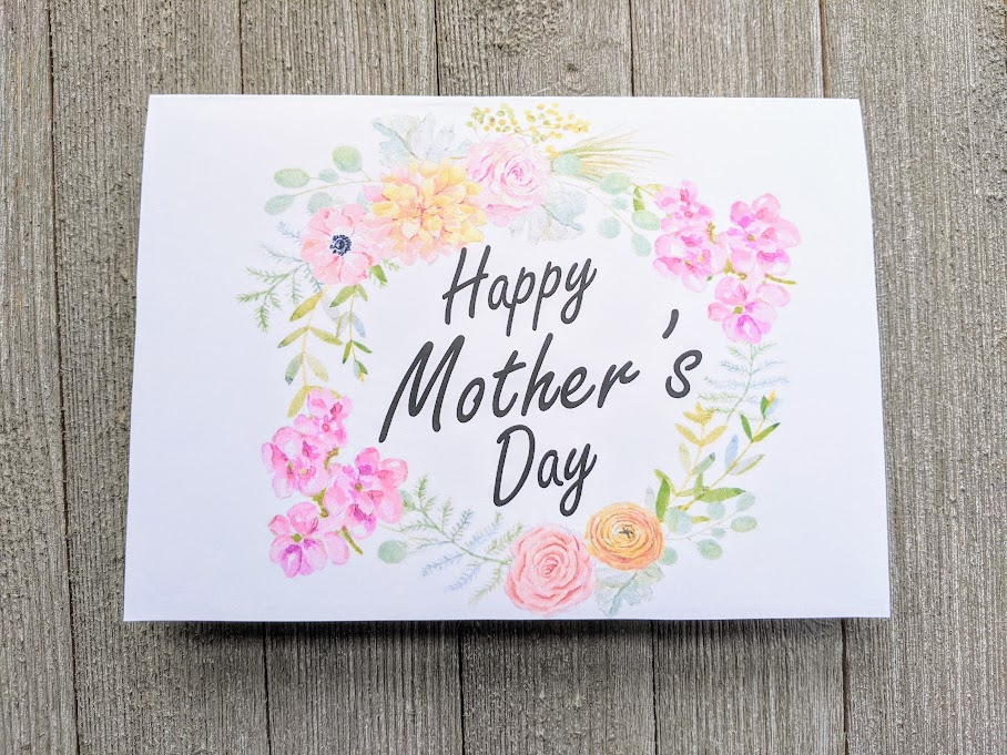 Overhead view of printable Mother's Day card printed out and folded. Front of card has a wreath of pink, yellow, and orange flowers with Happy Mother's Day in the center.