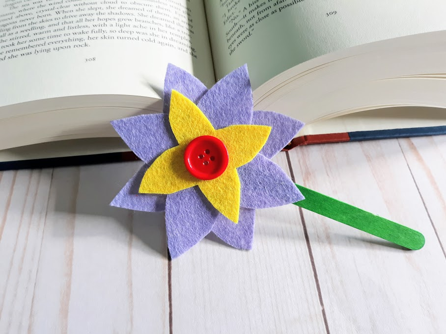 Purple and yellow felt flower with red button in the center attached to a green popsicle stick leaning against an open hardcover book.