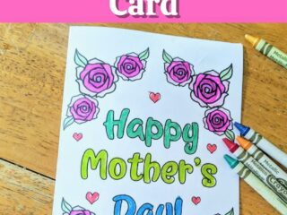 Top has white text outlined with black on a bright pink rectangle. Text reads Printable Mother's Day Card. Below text is a printed out card that says Happy Mother's Day colored in with blue and green marker. Words are surrounded by roses and small hearts colored in with crayons. Several crayons lay by card on table.