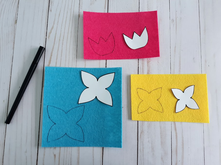 Tracing flower patterns on blue, yellow, and pink felt.