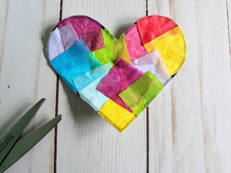 Close overhead view of completed small multicolored tissue paper heart suncatcher.