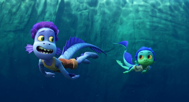 Still photo of Luca and Alberto swimming in sea monster form under water in the Disney Pixar movie Luca.