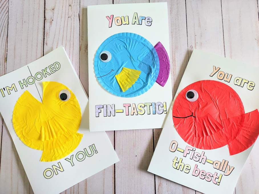 Overhead view of three completed fish pun card crafts. Three different printable cards with cupcake liner fish crafts on them. Left card says I'm Hooked On You with a yellow cupcake liner fish. Middle card says You Are Fin-Tastic with a blue, purple, and yellow cupcake liner fish. Right card says You Are O-fish-ally the best with a red cupcake liner fish.