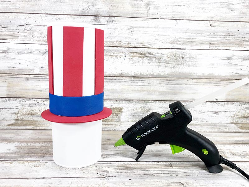 Red and blue craft foam pieces glued onto chip can painted white to make Uncle Sam's hat.