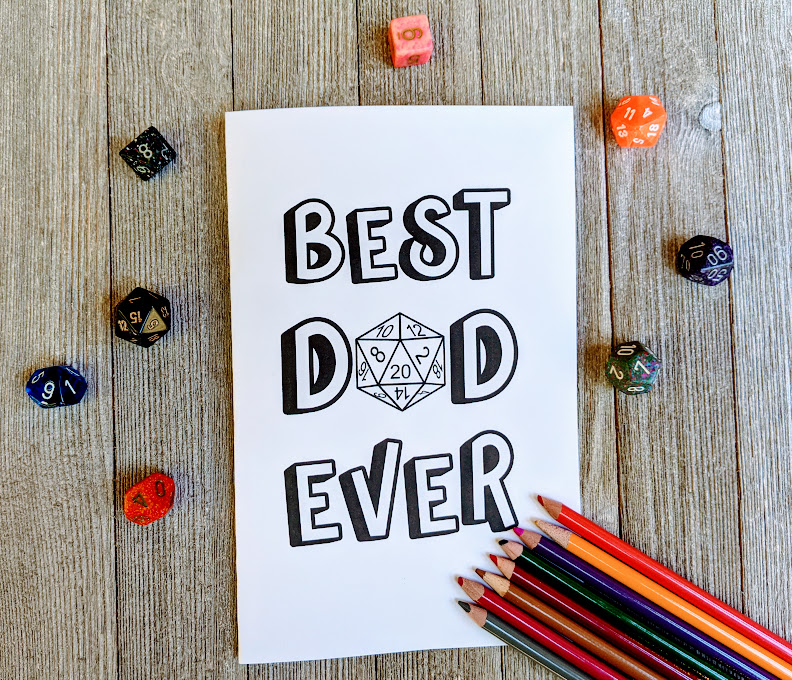 Overhead view of Best Dad Ever with a D20 in place of the A in Dad card printed out. Colored pencils lay lined up by the bottom right corner of the card. Assorted polyhedral dice for tabletop games are scattered around the card.