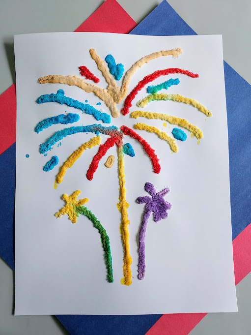 Overhead view of bright and colorful salt painting of fireworks using printable template. White paper with multicolored painted salt with red and blue construction paper underneath.