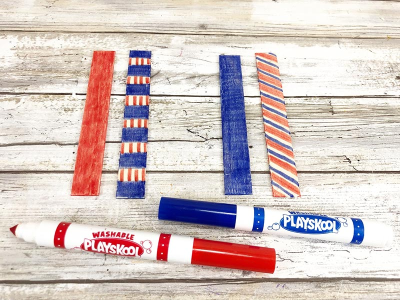 Four craft sticks with rounded ends cut off colored with red and blue markers.