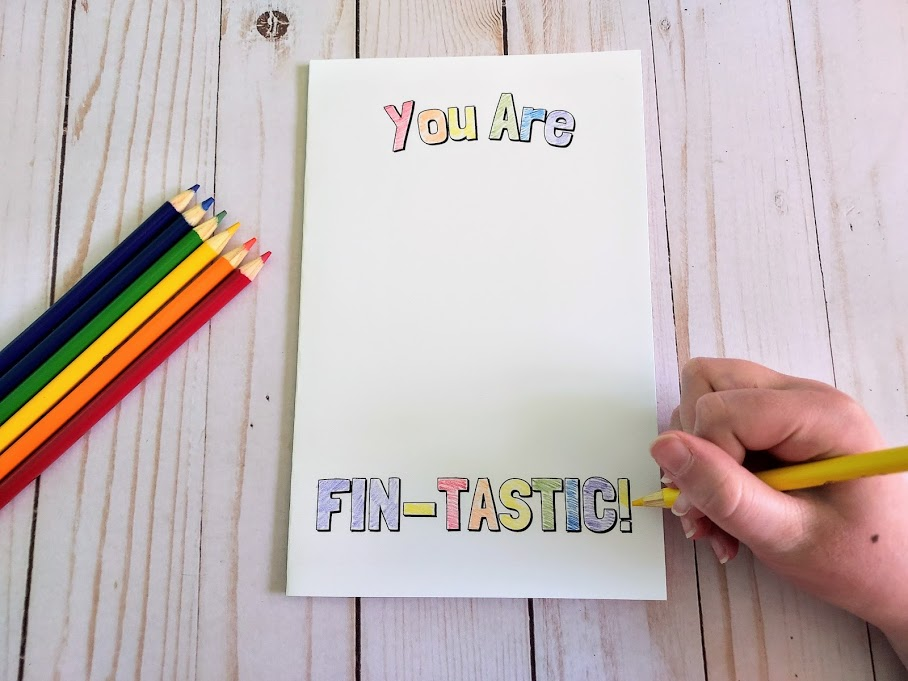 Overhead view of printable card that says You Are Fin-Tastic with colored pencils laying next to it. White girl's hand holding a color pencil and coloring in the words on the card.