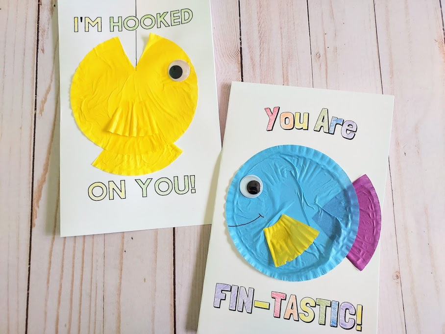 Two finished fish card crafts laying next to each other. Left card says I'm Hooked On You with a yellow cupcake liner fish with open mouth cut out and aimed at top of card. A black marker line drawn from top of card into the open fish mouth. Right card says You Are Fin-Tastic with a multicolored cupcake liner fish in the center.