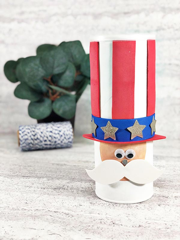 Completed Uncle Sam made from an empty Pringles chip can. Small green decorative plant and a role of black and white twine are in the background.