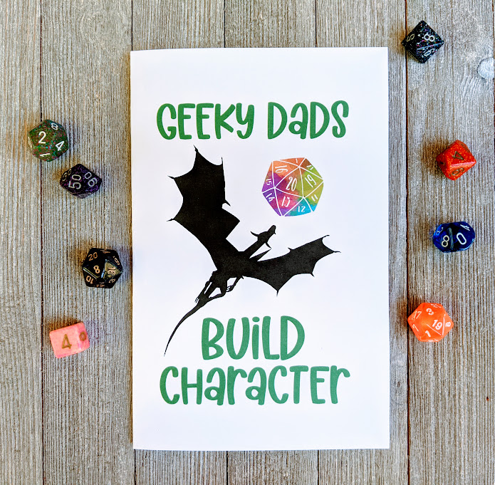 Overhead view of card printed out. Front of card has Geeky Dads in green text at the top, then a dragon silhouette flying towards a rainbow watercolor D20, and below the dragon is green text Build Character. Assorted polyhedral dice are scattered around the card.