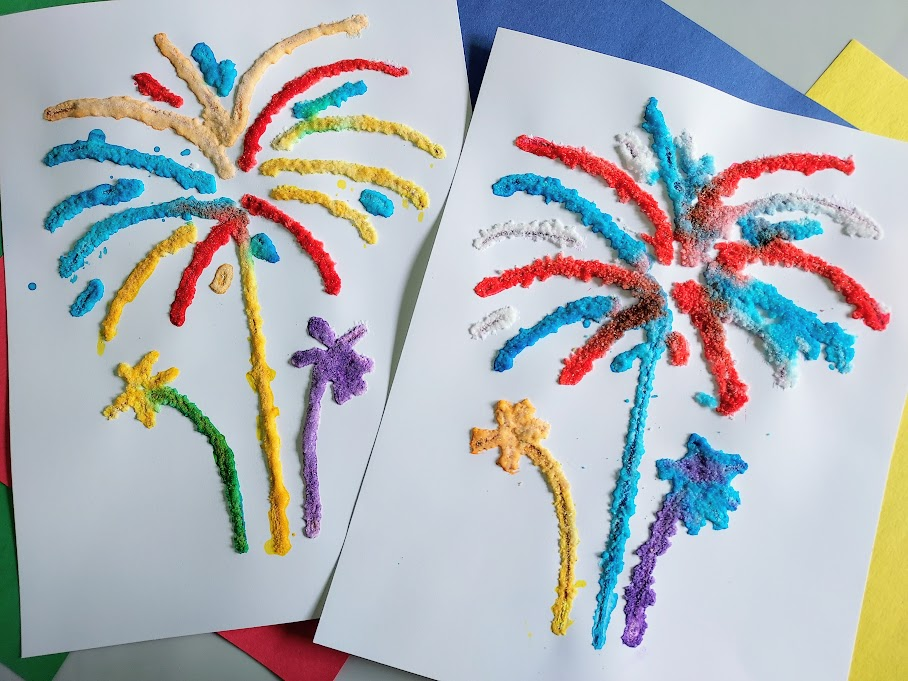 Two completed fireworks salt paintings using red, blue, yellow, purple, and orange watercolors. They lay on top of assorted colors of construction paper.