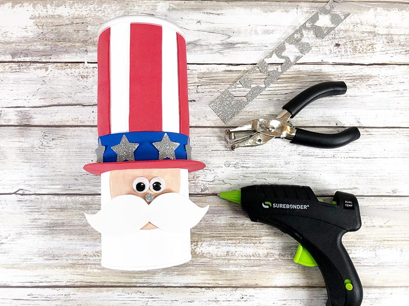 Uncle Sam chip can laying down showing eyes, nose, and mustache glued on and silver stars on hat band. Next to the project is a strip of silver glitter cardstock with stars punched out, a circle hand punch, and a hot glue gun.