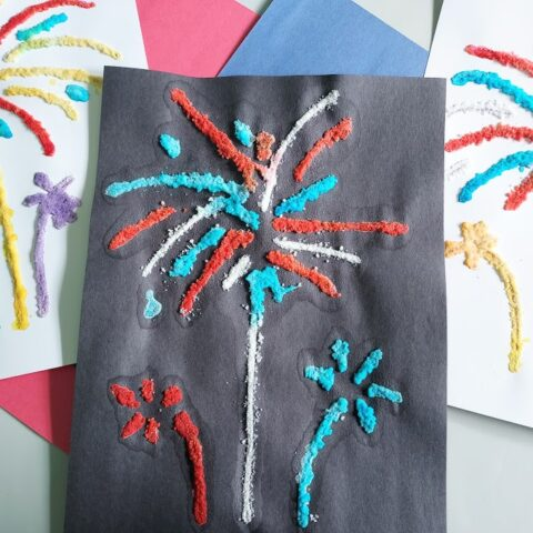 Three completed salt paintings of fireworks laying next to each other, slightly overlapped, on top of red and blue construction paper. Middle one is done on black construction paper using blue and red paints. The other two are on white paper and use a colorful variety of paints.