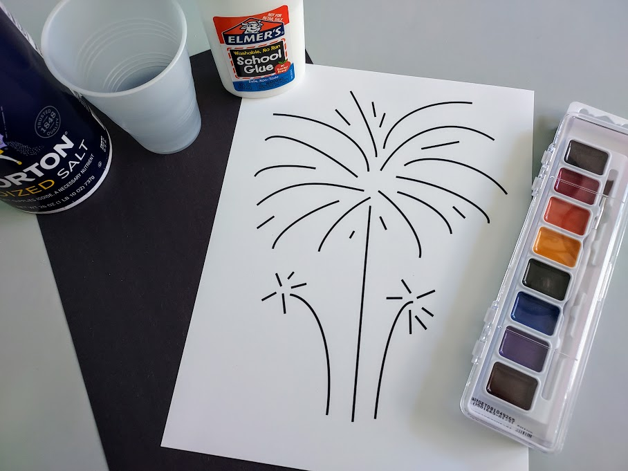 Overhead view of printed out fireworks template on white cardstock, a piece of black construction paper, water colors, liquid glue, cup of water, and container of table salt.