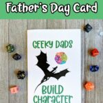 Black and white text on a green background at top says Printable Father's Day Card. Photo of printed out card that says Geeky Dads Build Character with a dragon and watercolor D20. Assorted dice are placed around the card.