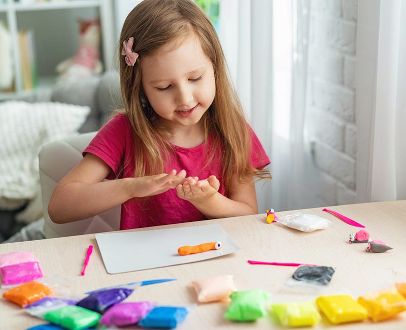 White girls with long brown hair sitting at a desk rolling modeling clay or playdough between her hands. Assorted colors of modeling clay on the desk.