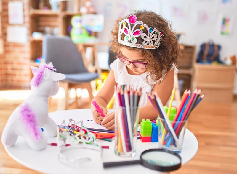 Young girl with curly brown hair, wearing glasses and a princess crown drawing at a table full of markers, colored pencils, magnifying glass, and a few toys.