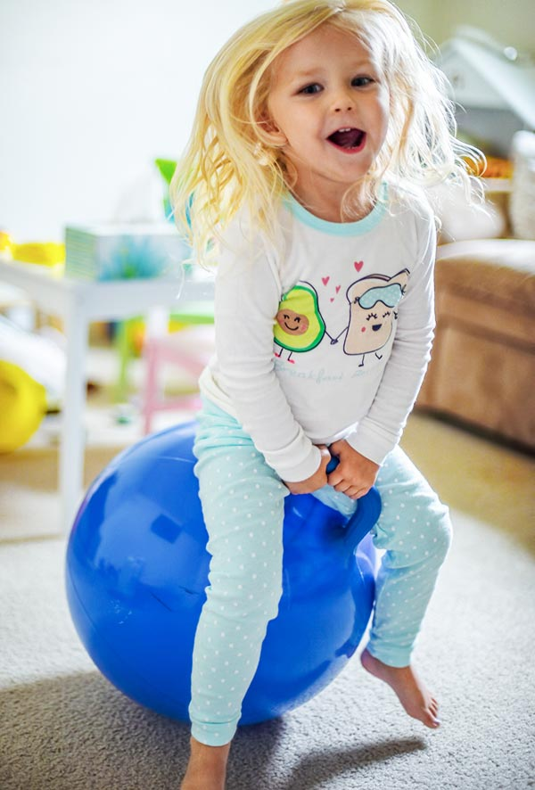 Young white blonde girl smiling and bouncing on a blue hopper ball toy in playroom.