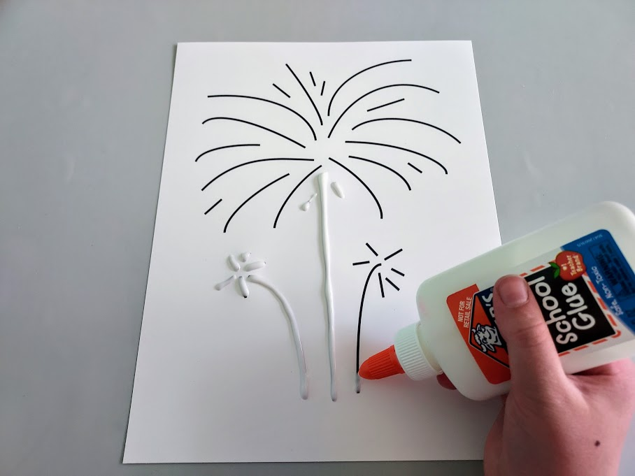 White girl's hand holding liquid glue bottle and squeezing glue along black lines of fireworks template.