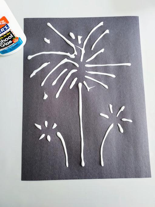 White glue lines in fireworks design on black construction paper.