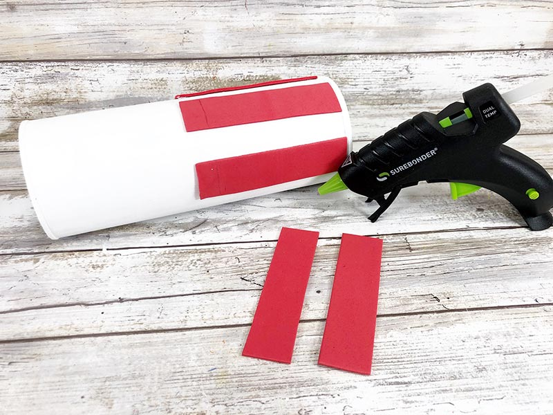 Hot gluing red craft foam pieces onto white painted chip can to make stripes.