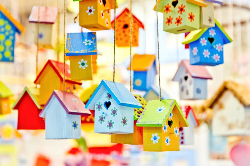 Numerous hanging wooden birdhouses painted with bright, vibrant colors.