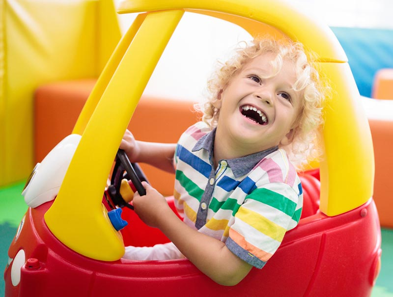 White preschool child with curly blonde hair laughing while inside red and yellow coupe car riding toy.