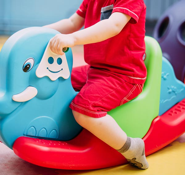 Side view of a toddler in red outfit from shoulders down on a rocking elephant toy.