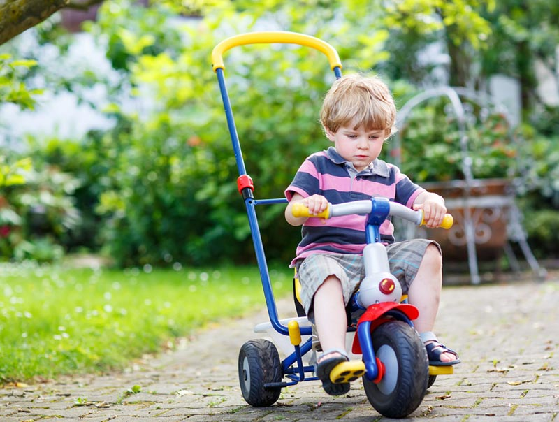 White child preschool age with short blond hair riding a tricycle with a tall handle bar in back for an adult to push. Kid is riding near a garden area.