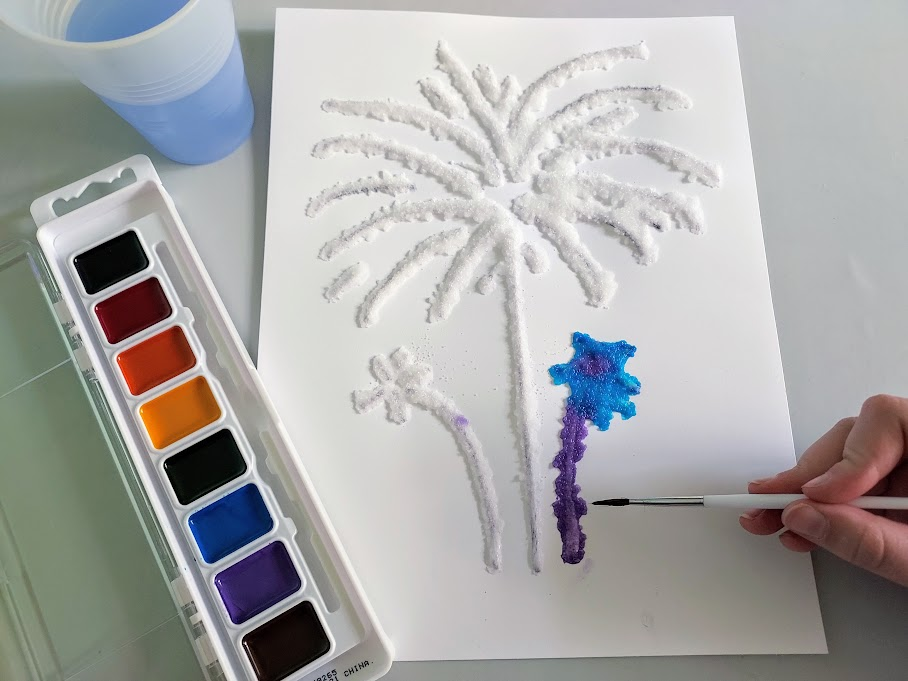 Overhead view of white girl's hand holding paintbrush and dabbing watercolor paints onto salt that's been glued to white cardstock paper in fireworks design.