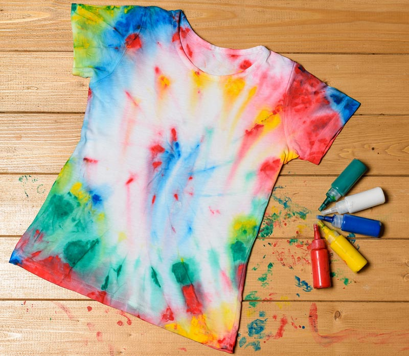Tshirt laying flat on wooden floor painted in tie dye style. Squeeze bottles of paint laying next to shirt and paint splatter on floor around shirt.