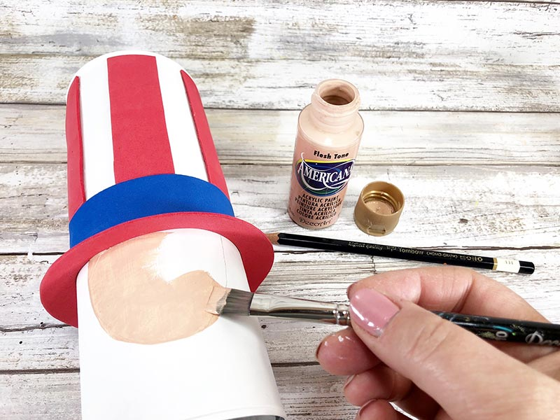 White woman's hand painting Uncle Sam's face onto chip can.