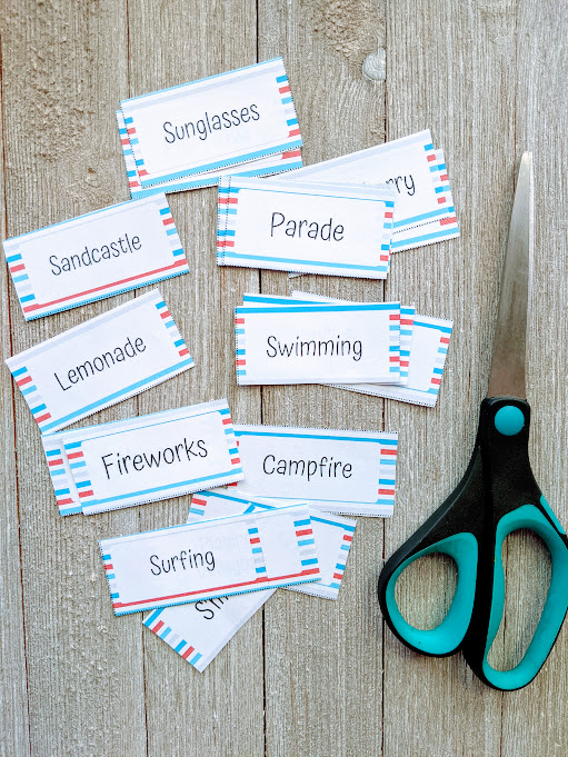 Summer themed drawing prompt cards cut apart and spread out on gray wooden table next to pair of scissors.