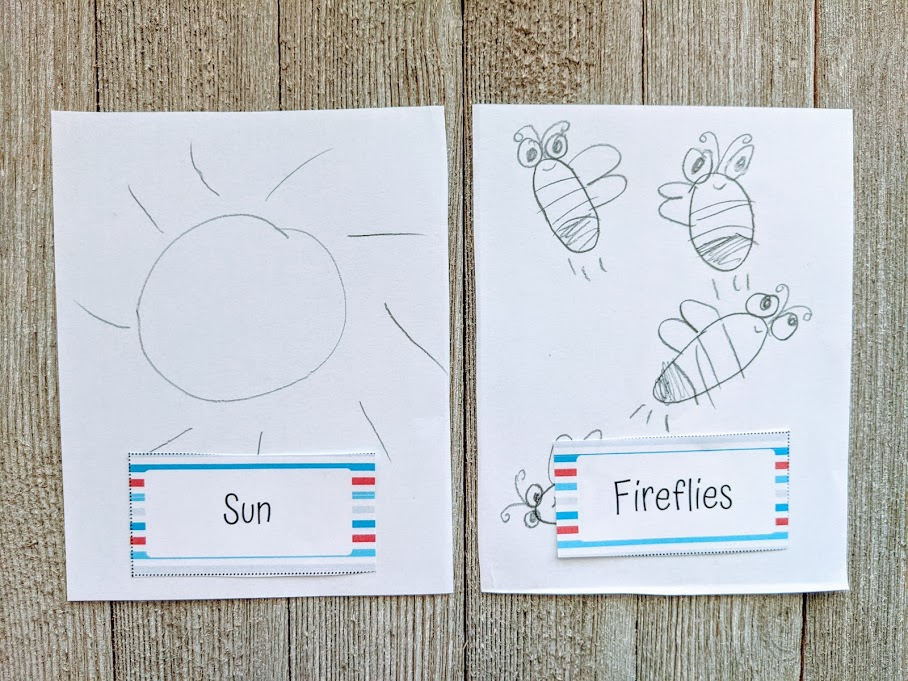 A sun and fireflies drawn in pencil by a child with the pictionary card laying at bottom of the drawings.
