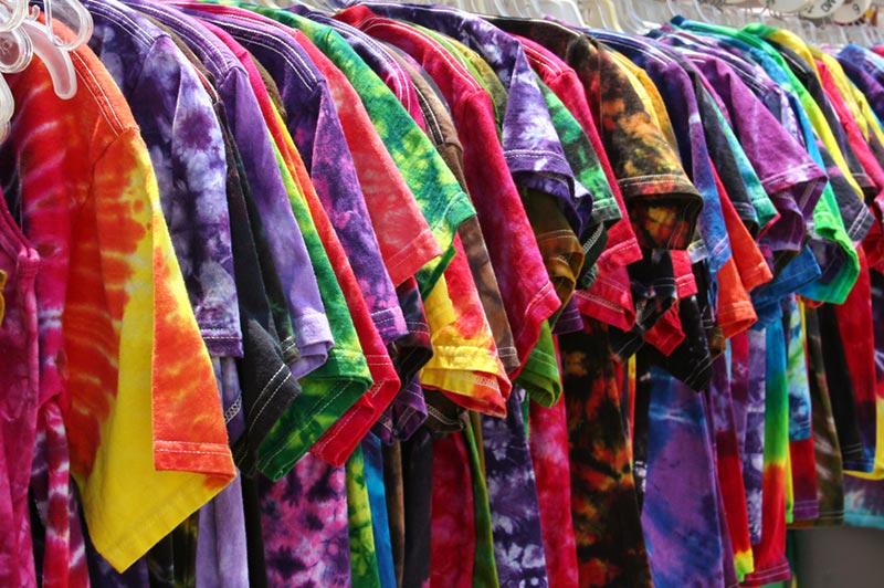 Angled side view of lots of tie dyed shirts on a clothing rack.